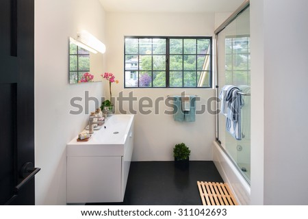 Modern bathroom with rectangle double white sink, transparent glass shower, mirror and towel.  - stock photo