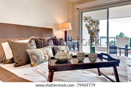 Modern bedroom in apartment  furnished with breakfast tray - stock photo