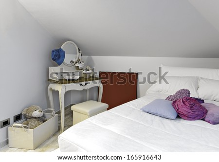 modern bedroom in the attic with colored pillows and wardrobe  - stock photo