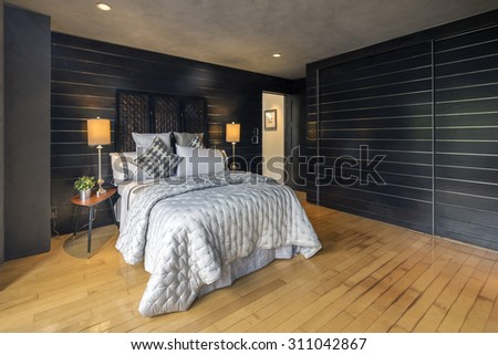 Modern bedroom interior in black / charcoal with light wooden floor and black wooden paneled sliding door closet in majestic home.  - stock photo