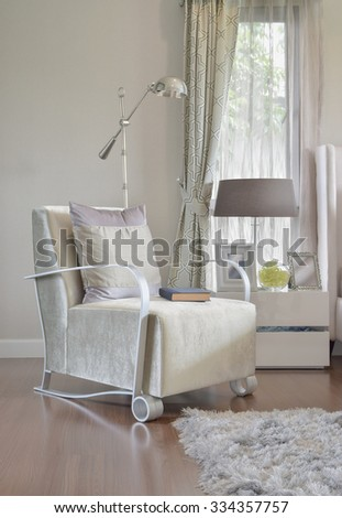 modern bedroom interior with gray pillow on armchair and bedside table lamp at home - stock photo