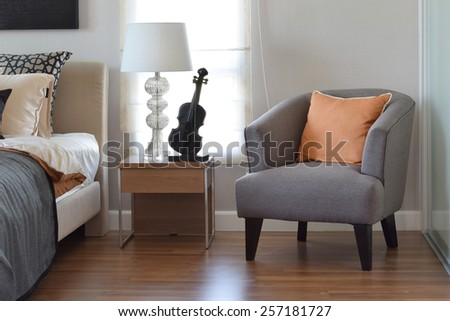 modern bedroom interior with orange pillow on grey chair and bedside table lamp at home - stock photo