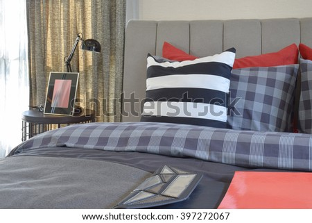 modern bedroom interior with striped pillow on bed and bedside table lamp at home - stock photo