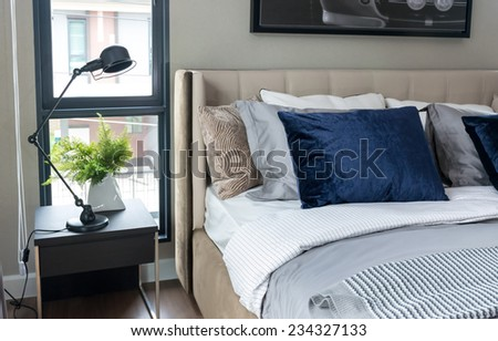 modern bedroom with blue pillows and black lamp on table - stock photo