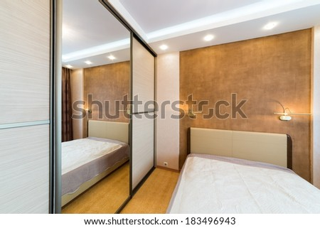 Modern bedroom with closet and large mirror - stock photo