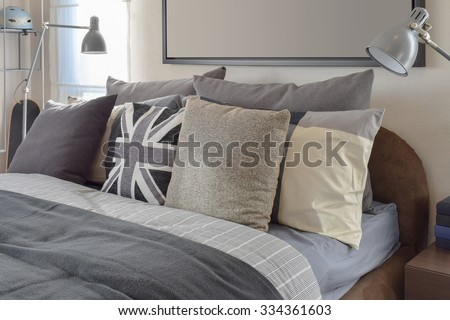 modern bedroom with gray pillow and lamp on wooden bedside table at home - stock photo