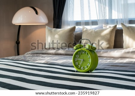 modern bedroom with green alarm clock on bed - stock photo