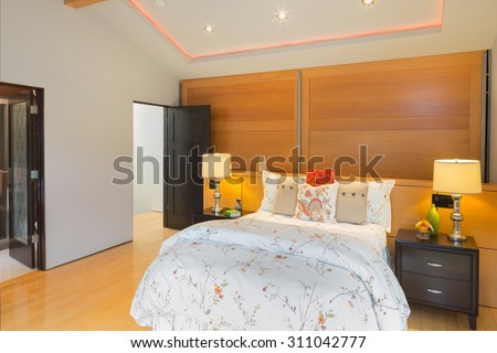 Modern bedroom with illuminated peaked ceiling, wooden floor and wooden accent wall.  - stock photo