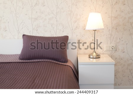 Modern bedroom with pillows and lamp - stock photo