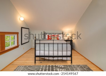 Modern bedroom with rug, window and wooden flooring with peaked roof and metal bed frame. - stock photo