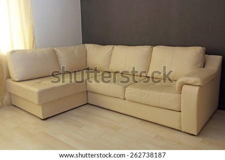 Modern beige corner leather sofa in livingroom. - stock photo