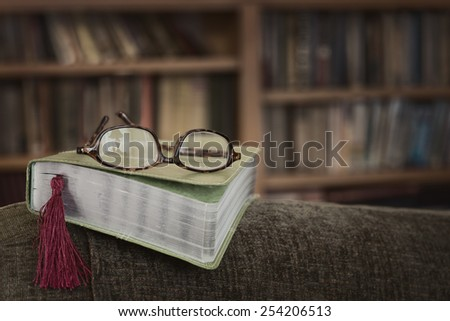 Modern Bible on Arm of a Chair with Reading Glasses with Lamp Reflection and Bookmark with Bookcase in Background with room or space for copy, text, your words.  Horizontal, moody sepia toned hue - stock photo