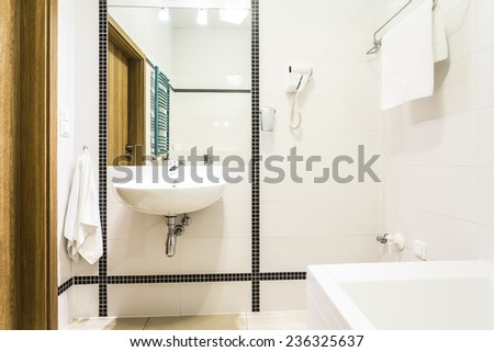 Modern black and white bathroom with turquoise radiator - stock photo