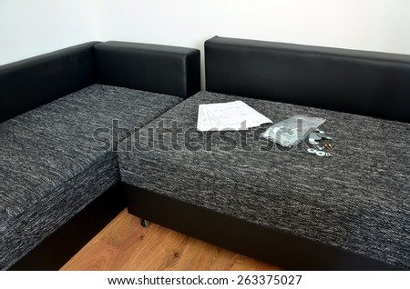 Modern black and white cloth sofa assembly, assembling parts of sofa and paper instruction - stock photo