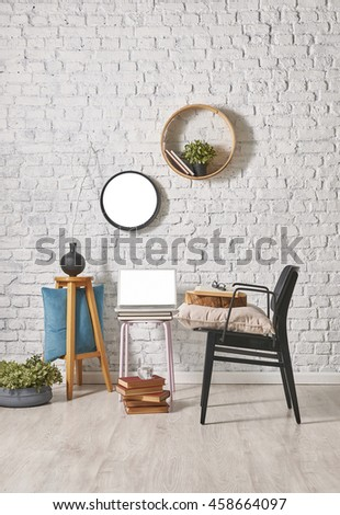 modern black chair and brick wall decor with round frame - stock photo