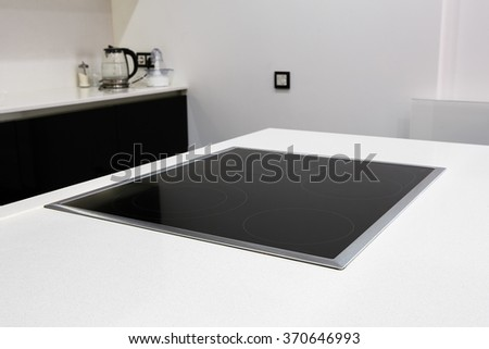 Modern black induction stove, cooker, hob or built in cooktop with ceramic top in white kitchen interior - stock photo