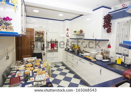 Modern Blue and white very bright and clean kitchen preparing food - stock photo