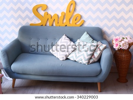 modern blue sofa in cozy bedroom with pillows and floor vase - stock photo