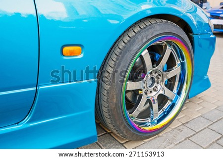 Modern blue sport car fragment, wheel on colorful metallic disc, closeup photo with selective focus and shallow DOF - stock photo
