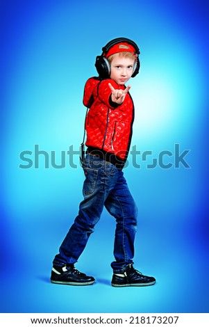 Modern boy listening to music in headphones and dancing. Fashion shot.  - stock photo