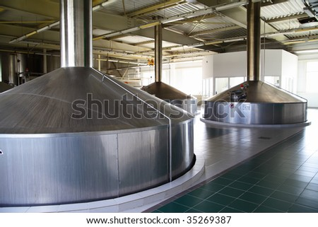 Modern brewery - workshop with steel fermentation vats - stock photo