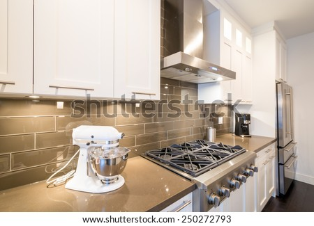 Modern, bright, clean, kitchen interior with stainless steel appliances in a luxury house. - stock photo