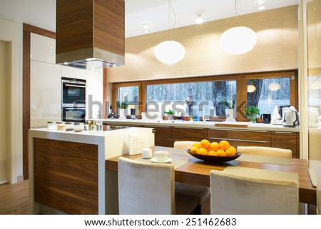 Modern bright wooden kitchen with island and big table - stock photo