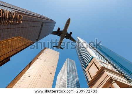 modern building underneath airplane , abstract cityscape in guangzhou  - stock photo