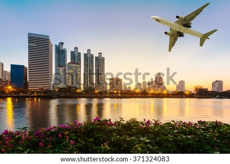 Modern building with flower and airplane under the sky at twilight in Bangkok, Thailand. - stock photo