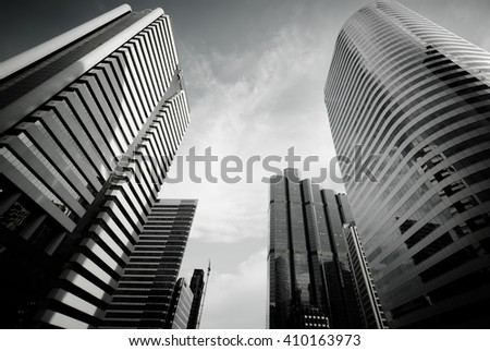 Modern building with sun flare at Bangkok City, Thailand. Bottom view of Modern business skyscrapers. Concepts of banking, financial, economics, future. Monochrome black and white color. - stock photo