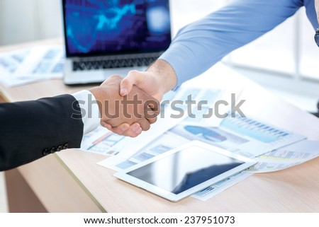 Modern business handshake. Close-up view of a handshake while two successful businessman shaking hands at the table against each in the business office in formal wear and work at a laptop. - stock photo