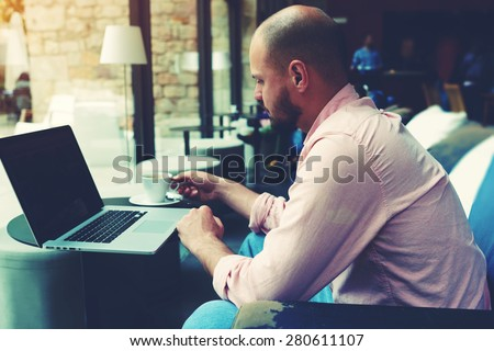 Modern business man connecting to wireless on his laptop computer during coffee break in modern interior, male freelancer working on notebook sitting in cafe, entrepreneur hold cup of tea or coffee - stock photo