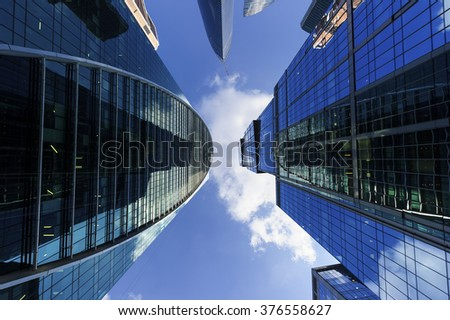 Modern business office skyscrapers, looking up at high-rise buildings in commercial district, architecture raising to the blue sky with white clouds, bottom view  - stock photo