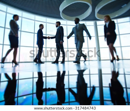 Modern business people against window in office building - stock photo