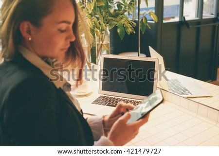 modern business woman discussing work issues in a chat on the phone during the lunch break. focus on laptop. Young girl sitting in front open net-book with copy space screen for your text or content.  - stock photo