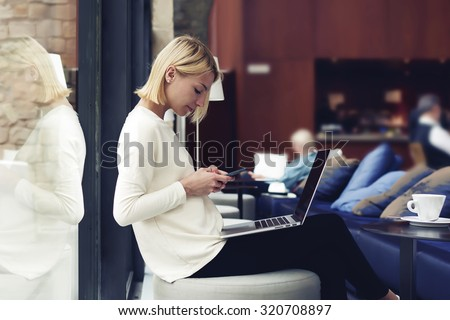 Modern business woman or successful working on smart phone and laptop computer at coffee shop interior, female student sitting in university library while using technology, internet distance work - stock photo