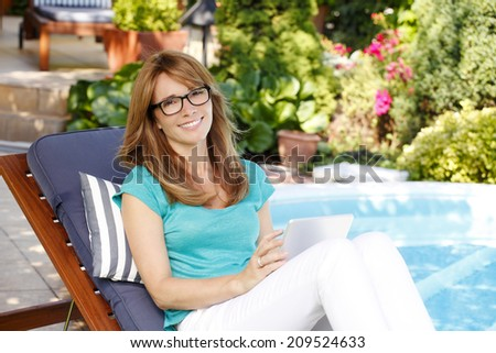 Modern business woman with digital tablet sitting at garden and working at home. Small business. - stock photo