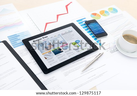 Modern business workplace with business news website on digital tablet, mobile banking on a smartphone and some charts and graphs on a desktop. - stock photo
