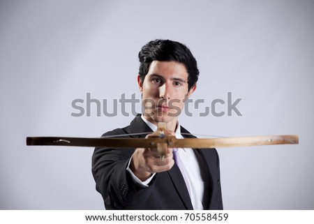 Modern businessman aiming with a crossbow - stock photo