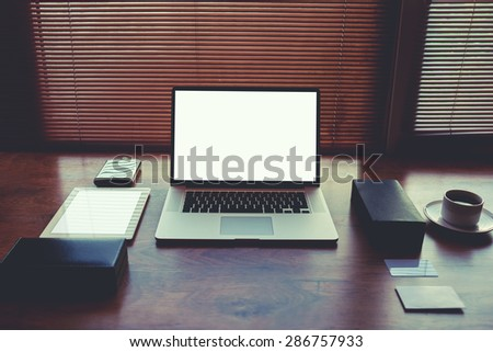 Modern businessman or entrepreneur workspace table with style accessories and coffee cup, open laptop computer and digital tablet with white blank copy space screen for text information or content - stock photo