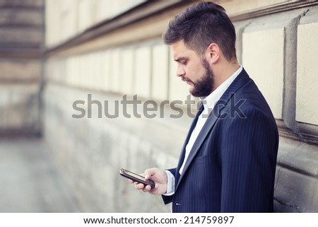 Modern businessman sending text message with his mobile phone in front of the wall - stock photo