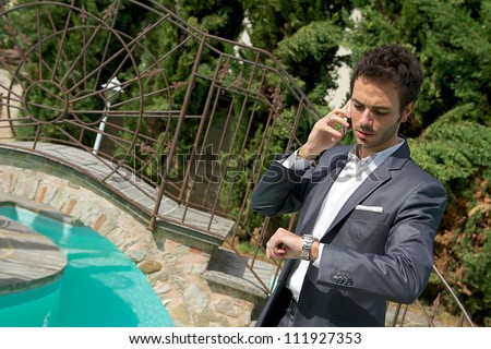 Modern businessman talking on phone and looking on watch - stock photo