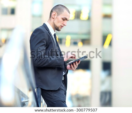 Modern businessman using digital tablet. Man working for digital tablet on the background office center building. Working out of the office. Manager, businessman working for pad. Electronic tablet. - stock photo