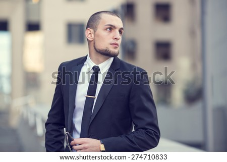 Modern businessman. Young man of arabic origin in a suit. Business man in the background office building. Confident businessman portrait. Confident and charismatic modern business man. Look toward. - stock photo