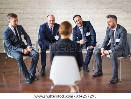 Modern businessmen listening to colleague answering to their questions - stock photo
