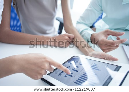Modern businesspeople discussing the progress shown through digital graphs - stock photo
