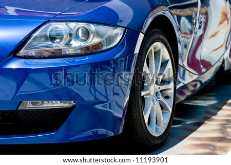 modern car in reflections on blue metallic - stock photo