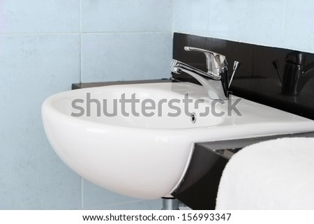 Modern ceramic hand wash basin with chrome water mixer tap in hotel washroom interior  - stock photo