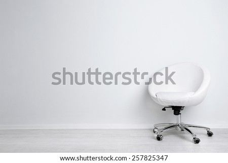 Modern chair on white wall background - stock photo