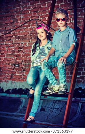 Modern children wearing casual jeans clothes posing on the city street by a brick wall. Kid's fashion. - stock photo